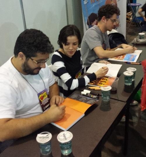 Eduardo Damasceno (esquerda), conversando com Lu Cafaggi (centro). Ao fundo, Vitor Cafaggi
